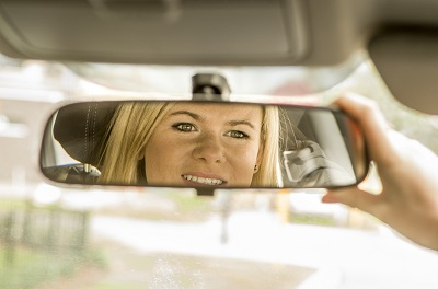 Young girl looking in rear view mirror.