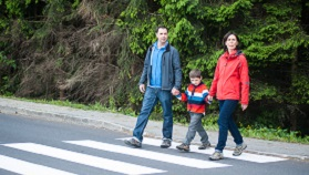 Parents walking son across road